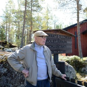 Pentti Kronqvist in front of an old wooden church.