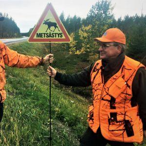 Kaksi metsästäjää kyltin kanssa.