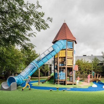 Ett runt, högt blåfärgat hus i en lekpark, ett så kallat muminhus. Huset har också en rutschkana.