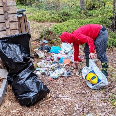 nainen keräämässä roskia mökin vieressä