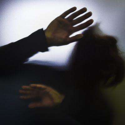 Kuvituskuvassa ihmisen käsi on painautunut lasia vasten.