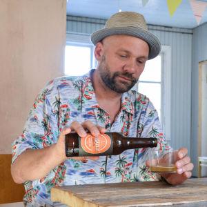 Mikko Airas häller öl från en flaska i ett glas