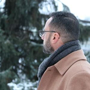 En man i brun rock tittar bort från kameran.