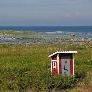 Bild från Kvarkens skärgård. Ett rött dass står i förgrunden.