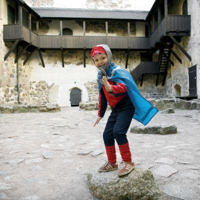 Lapsi pukeutuneena hämähäkkimiehen pukuun ja ritarin viittaan.