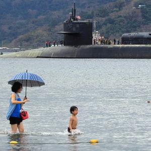 Människor badar på stranden i bakgrunden militärubåten USS Michigan.