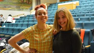 Två unga kvinnor tittar in i kameran och ler. I bakgrunden synns sittplatser i en konsertsal.
