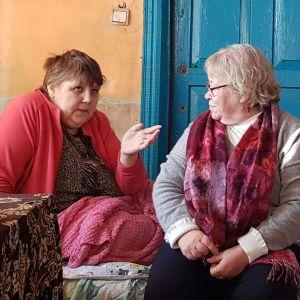 Frivilligarbetare talar med sjuk kvinna i säng