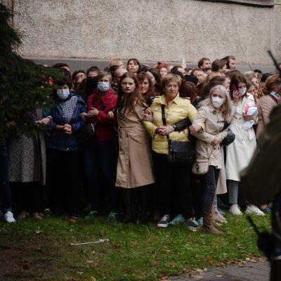 Kuvassa Minskissä on rykelmä naisia, etualalla seisoo tumma poliisihahmo.
