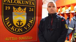 En man i blå jacka står i ett omklädningsrum för räddningspersonal. Bakom honom hänger skyddsutrustning på rad och till vänster har han en skylt där det står Valkon VPK palokunta.