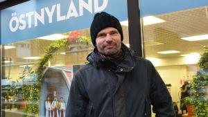En man i mörk jacka och mössa står utanför Östnylands redaktion. Bredvid honom i fönstret hänger fotografier där man ser lucia och tärnor.
