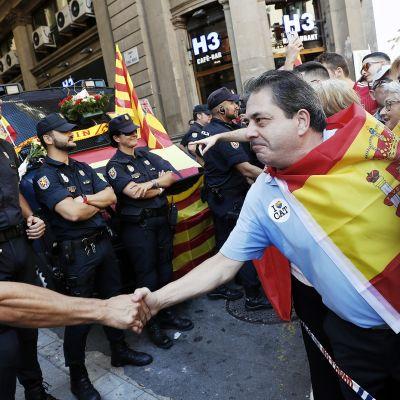 Poliisi kättelee Espanjan yhtenäisyyttä kannattavia mielenosoittajia Barcelonassa.