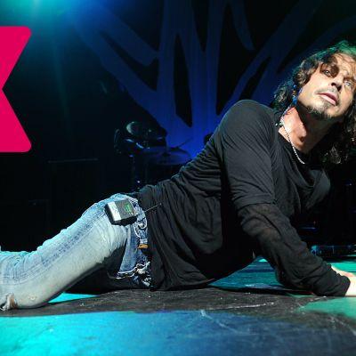 Chris Cornell ligger ner på scenen och lutar sig mot ena armen med huvudet höjt.
