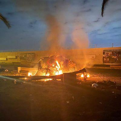 Ohjusiskussa tuhoutuneen ajoneuvon jäänteet palavat Bagdadin lentoasemalla.