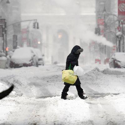 Henkilö kävelee lumimyräkässä New Yorkissa.
