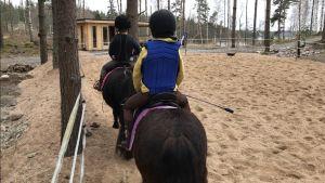 barn som rider på hästar.