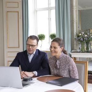 Kronprinsessan Victoria och Prins Daniel deltar i ett videomöte med en laptop framför sig.