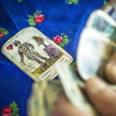 Tarot-kortteja pöydällä ja henkilön käsissä.