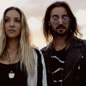 Zibbz-duo seisoo auringolaskumaiseman edessä, naisella vaaleat hiukset ja miehellä tummat, hänellä myös parta ja vaaleat aurinkolasit.