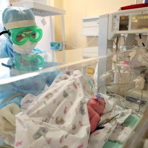 suojapukuinen työntekijä huolehtii vastasyntyneestä