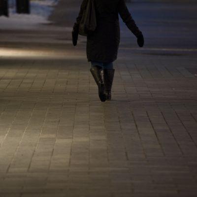 Nainen kävelee hämärällä kävelykadulla.