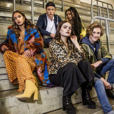 Sarjan päähahmot, nuoret lukiolaiset, istuvat jäähallin katsomossa katsoen kameraan. Kolme tyttöä ja kaksi poikaa.