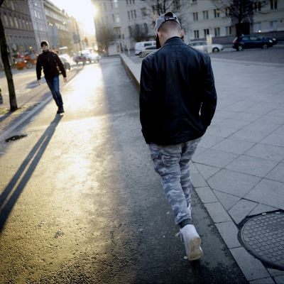 Nuori kävelee yksin kadulla.
