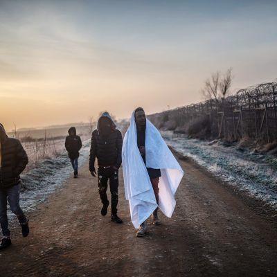 Siirtolaismiehet kävelevät kohti Kreikan rajaa.
