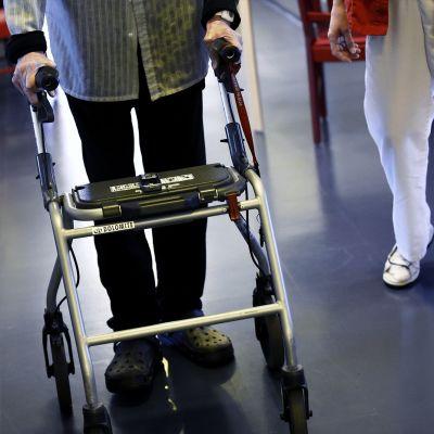 Asukas ja hoitaja kävelevät hoivakodin käytävällä.