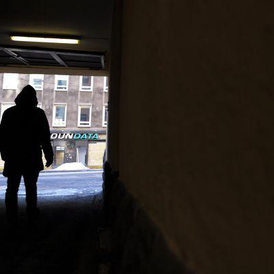 Henkilö kävelee pimeässä porttikongissa kohti valoisampaa katunäkymää.