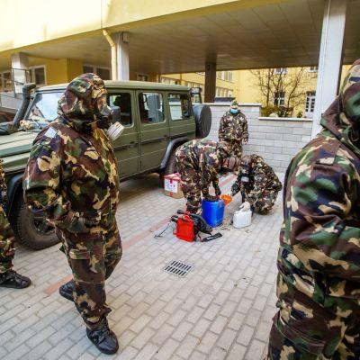 Suojapukuisia sotilata tulossa desinfioimaan koulua.