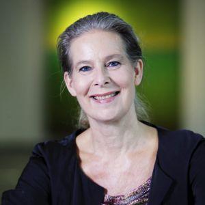 Anna Nohynek tittar in i kameran. Bakom henne en grön bakgrund. Hon har grått hår och ler med såväl munnen som ögonen.