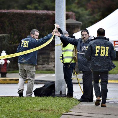 FBI:n väki ja muutama siviilihenkilö tarkastelee Tree of Life -synagogan ulkopuolella olevaa aluetta 28. lokakuuta.