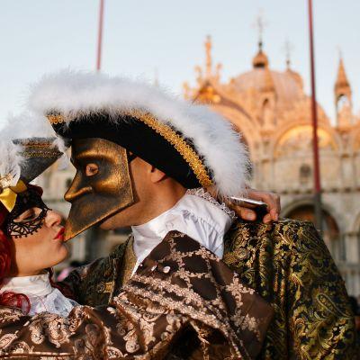 KArnevaaliasuihin pukeutuneet nainen ja mies suutelevat Venetsiassa.