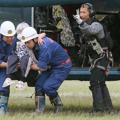 Pelastajat nostavat vanhusta laskeutuneesta helikopterista.