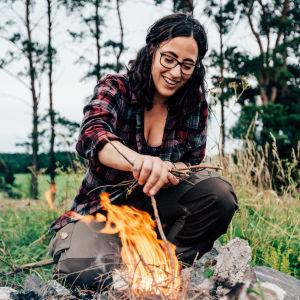 En kvinna som gör upp en eld.