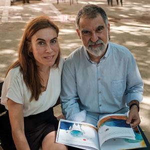 Kuvaa Barcelonan kaduilta. Mies ja nainen istuu puiston penkillä kirja sylissään ja katsoo kameraan.