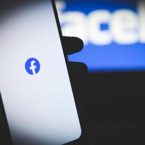 Facebookin logo kännykän ruudulla, kuvan taka-alalla sumeana teksti Facebook.