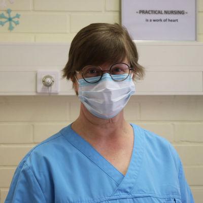 Kvinna i glasögon och munskydd och blåa vårdkläder tittar in i kameran.