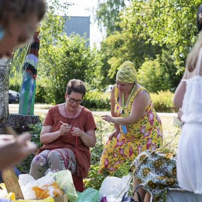 Neulegraffitityöpajan ohjaaja Outi Pantsar neuvoo Taina Pellistä Ääniä-istuinalusen aloittamisessa.