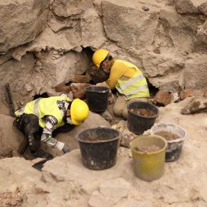 Två personer jobbar på arkeologiska utgrävningar i Katedralskolan i Åbo.