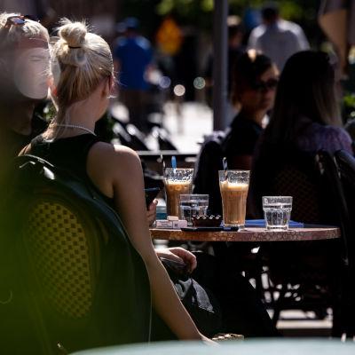 Anonyymi ihminen juo kahvia aurinkoisella terassilla.