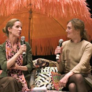 Katja Lindroos haastattelee muotoilija Inga Sempéä oranssin päivänvarjon alla.