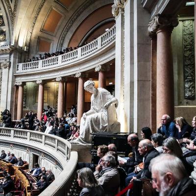 Människor följer med diskussion om eutanasi i parlamentet i Portugal. På bilden syns en gammal sal med gipsstatyer och pelare.