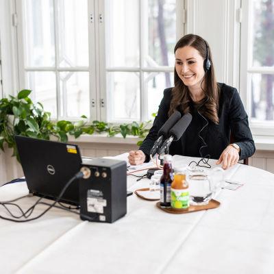 Sanna Marin håller distansmöte vid ett bord i Villa Bjälbo. Framför henne står några flaskor saft.