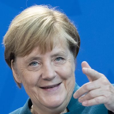 Angela Merkel pekar med pekfingret mot kameran och ler.