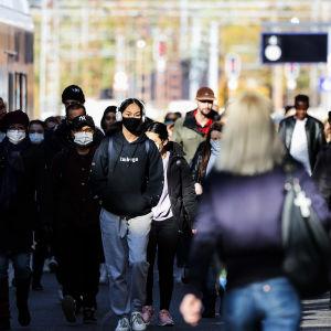 Många människor promenerar utomhus med ett tåg längst till vänster på bilden. En del bär munskydd.
