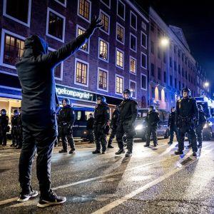En demonstrant står vänd mot polisen.