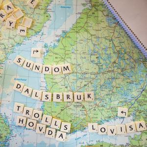 En karta över Finland med orterna Sundom, Dalsbruk, Trollshovda och Lovisa stavade med Alfapet-brickor.