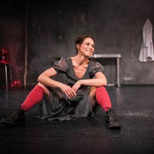 Tanssija, koreografi Hanna Brotherus näyttämöllä istumassa harmaassa mekossa ja punaisissa polvisukissa.